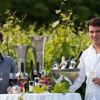 Philipp und Andreas Brummund mit Weinflaschen am Tisch.