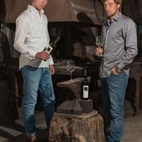 Die Brüder Brummund mit Weinflaschen in der Schmiede.