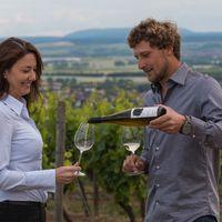 Philipp giesst Sabine Brummund Wein ins Glas.