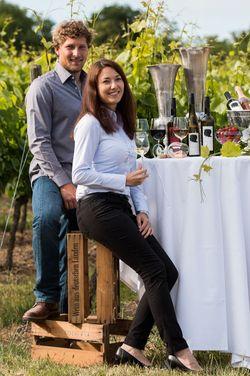 Philipp und Sabine Brummund stehen an Tisch mit Weinflaschen.